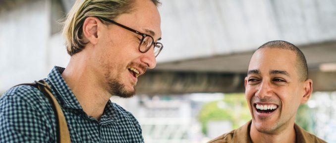 Zwei gitgelaunte Männer , von den einer eine Brille trägt