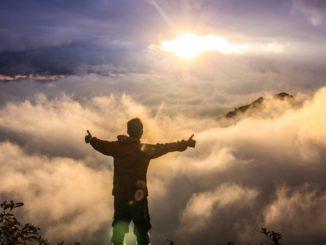 Mann mit ausgebreiteten Armen auf Berggipfel