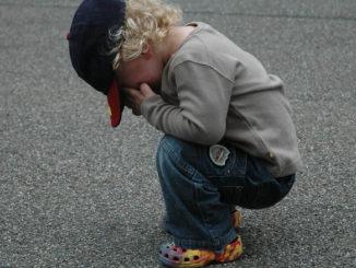 Hockendes Kind, das weint