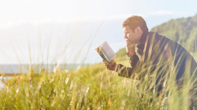 Mann, der im Gras sitzend, ein Buch liest