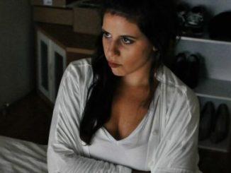 nachdenklich-traurie Frau auf Bett sitzend