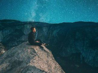 Mann sitzt auf Fels