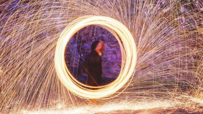 Mensch in goldenem Kreis aus Feuerwerk