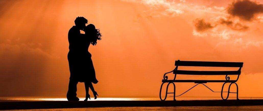 Paar, dass sich in Abenddämmerung küst