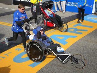Laufender Mann mit Sohn im Rollstuhl