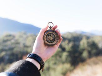 Hand, die einen Kompass hält