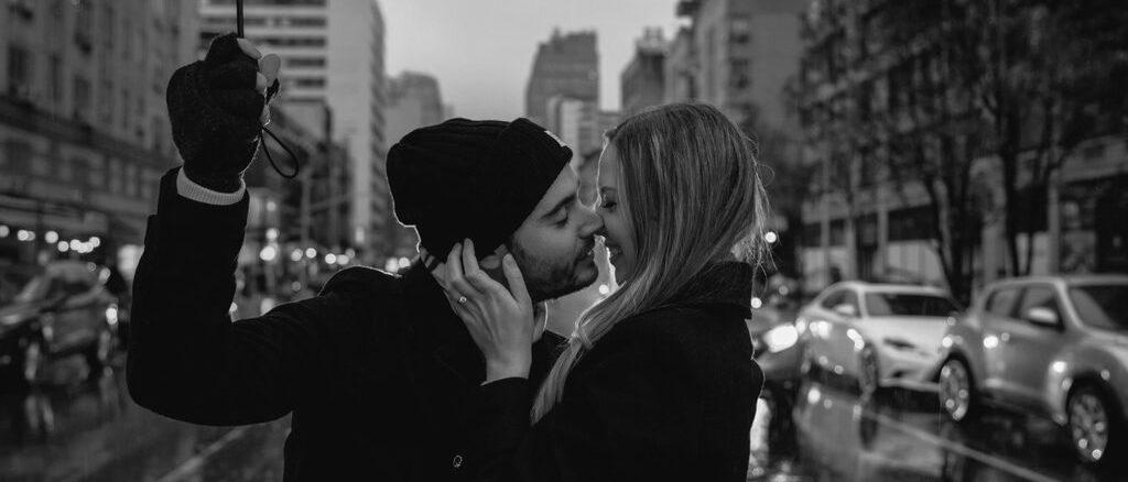 Paar, dass sich bei Regen unter Schirm küsst