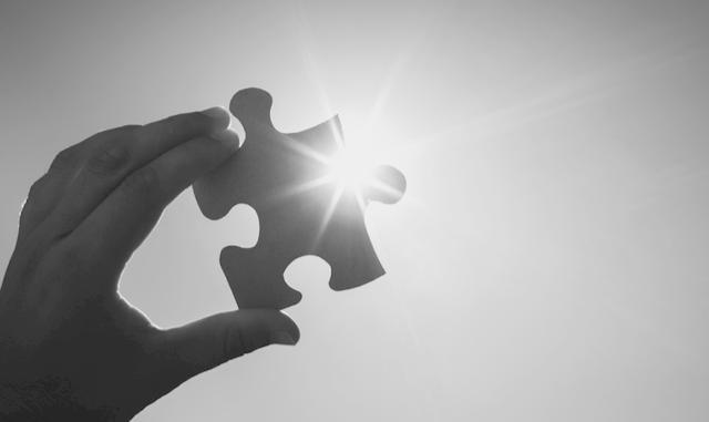 Hand, die Puzzleteil fesrhält
