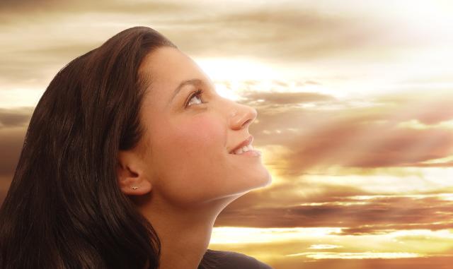 Frau, die optimistisch in wolkigen Himmel schaut