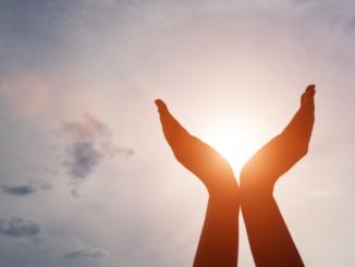 Gefaltete Hände vor aufgehender Sonne