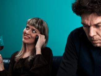 Frau telefoniert und trinkt Rotwein, während Partner wortlos dabei sitzt