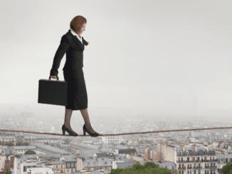 Frau im Businessoutfit auf Hochseil über einer Stadt balancierende